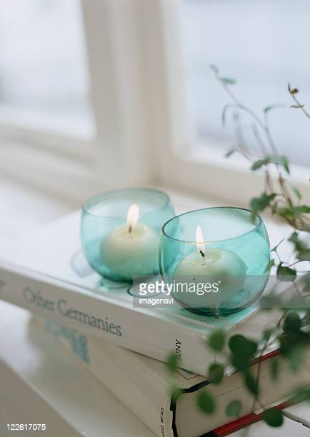 Lighted candles and books
