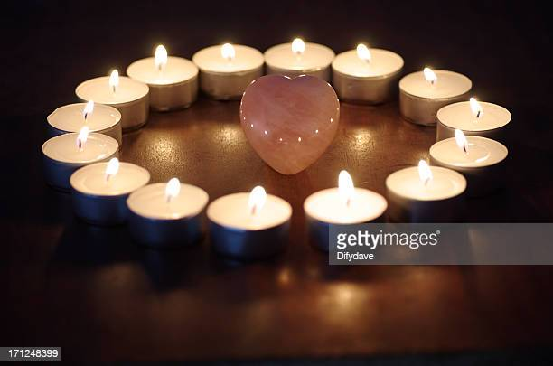 lighted candles on polished wood around heart shaped rose quartz - rose quartz stock pictures, royalty-free photos & images