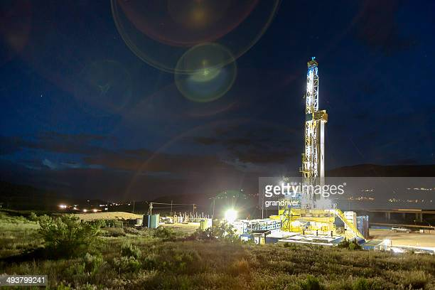 lighted drilling fracking rig at night - fracking stock pictures, royalty-free photos & images