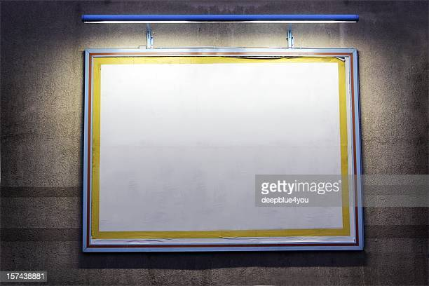 Cartel iluminado al aire libre, en una pared en la noche