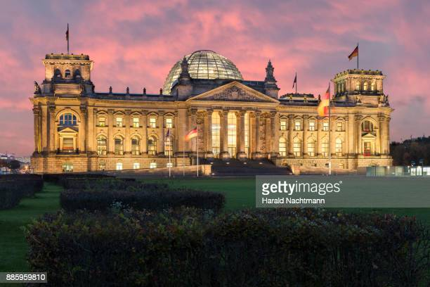 lighted reichstag at night - bundestag stock photos and pictures