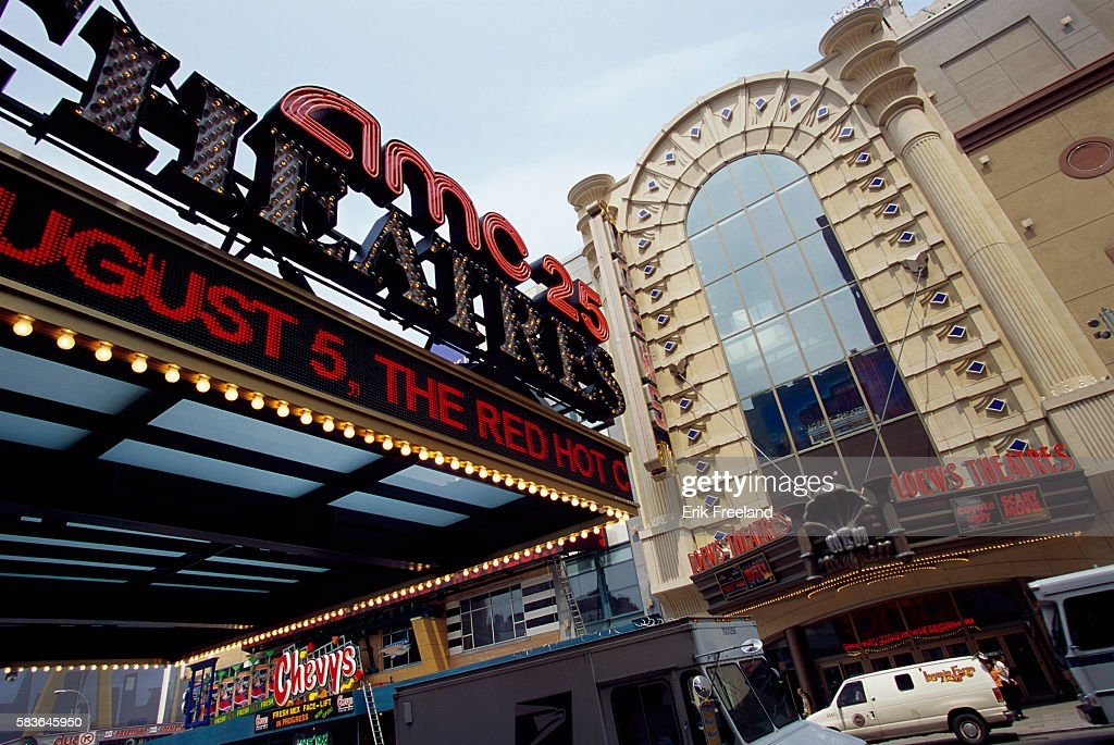 Lighted signs cover the marquee in front of the AMC Empire 25 movie