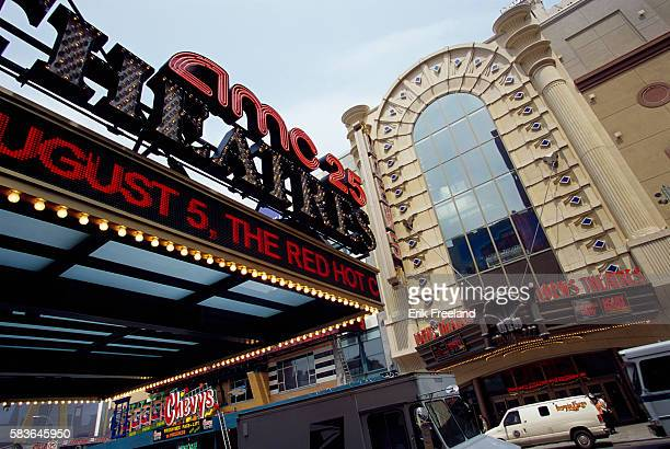 Lighted signs cover the marquee in front of the AMC Empire 25 movie theater on 42nd Street at the edge of Times Square Across the street is the Loews...