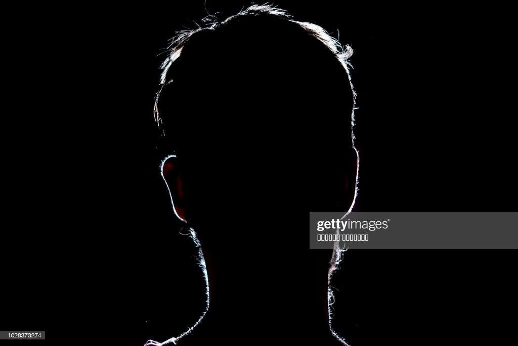 lighten portrait silhouette of a human head in the dark  background : Stock Photo