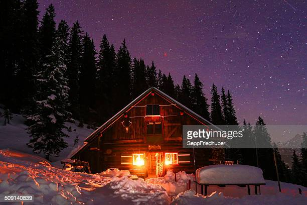 lightened mountain hut in the austrian alps with milky way - hut stock pictures, royalty-free photos & images