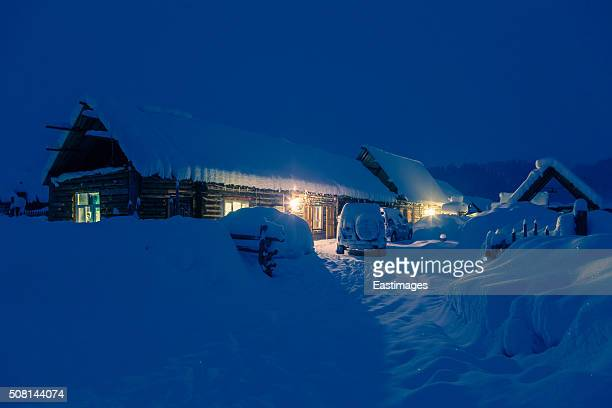 Lightened wooden house in a world of ice and snow at night/Xinjiang,China.