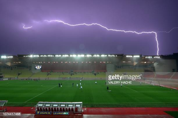 TOPSHOT Lightening sparks in the sky atop of the Louis II stadium as Monaco's teamplayers warm up before a French League Cup football match between...