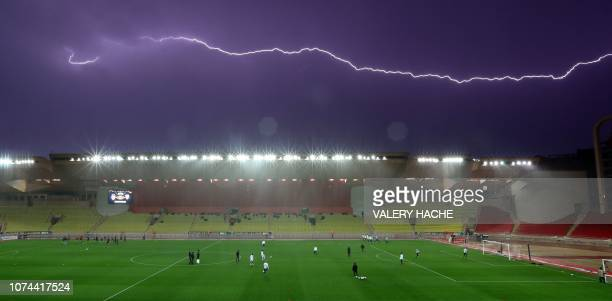 Lightening sparks in the sky atop of the Louis II stadium as Monaco's teamplayers warm up before a French League Cup football match between Monaco vs...