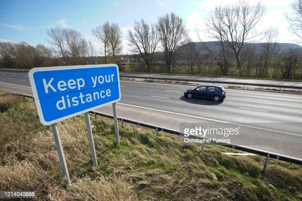 Lighter than normal traffic passes a safety sign declaring 'Keep your distance' on the M56 motorway in Cheshire on March 22 2020 in Runcorn United...