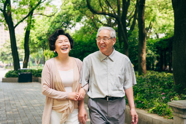lighthearted chinese seniors walking at a shanghai park - asian old couple in the park stock pictures, royalty-free photos & images