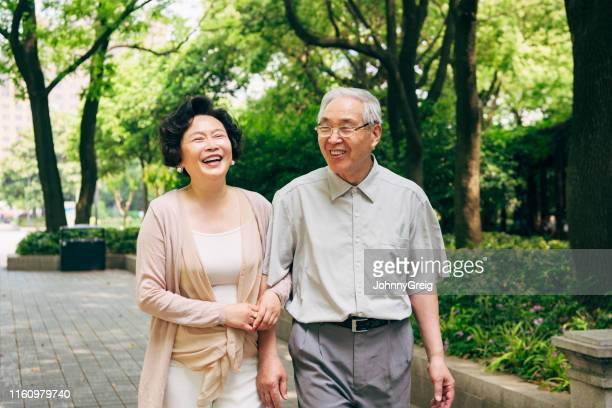 lighthearted chinese seniors walking at a shanghai park - chinese ethnicity stock pictures, royalty-free photos & images