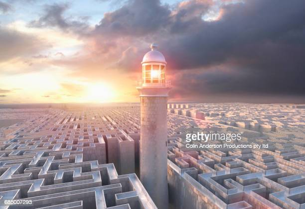 Lighthouse above distant maze at sunset