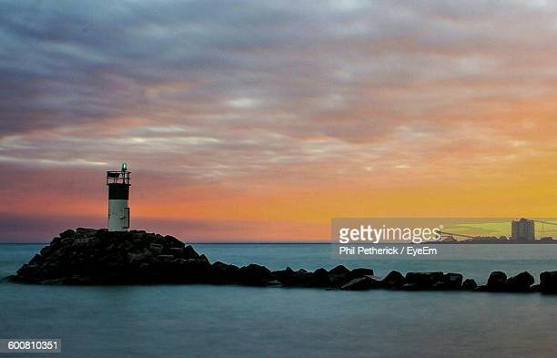 lighthouse amidst sea against sky during sunset - oshawa stock photos and pictures