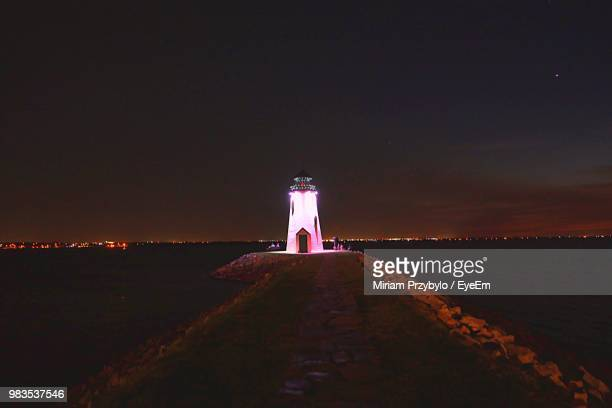 lighthouse amidst sea and buildings against sky at night - oklahoma city stock pictures, royalty-free photos & images