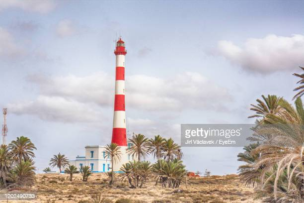 lighthouse amidst trees and buildings against sky - djerba stock pictures, royalty-free photos & images