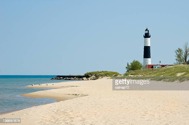 lighthouse and beach sand along shoreline, michigan great lakes scenery - lake michigan stock pictures, royalty-free photos & images