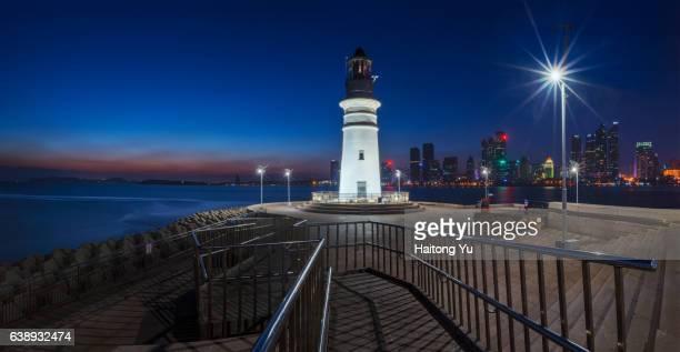 Lighthouse and city skyline at twilight