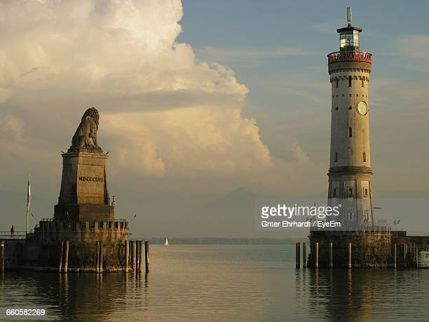Lighthouse And Lion Statue Against Sky At Bodensee