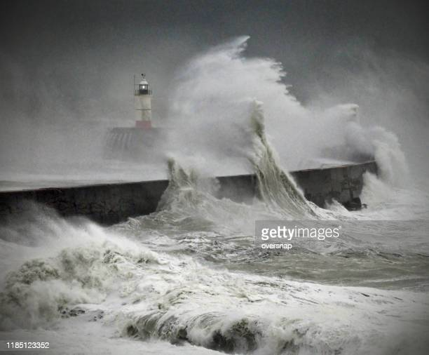 lighthouse and ocean storm - extreme weather stock pictures, royalty-free photos & images