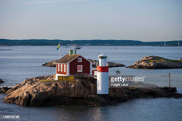 lighthouse and red house on rocky island in gothenburg archipelago, near goteborg. - archipelago stock pictures, royalty-free photos & images