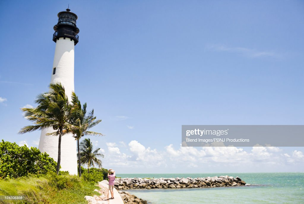 Lighthouse and tropical palm trees near ocean : Stock Photo