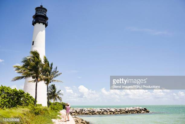 Lighthouse and tropical palm trees near ocean