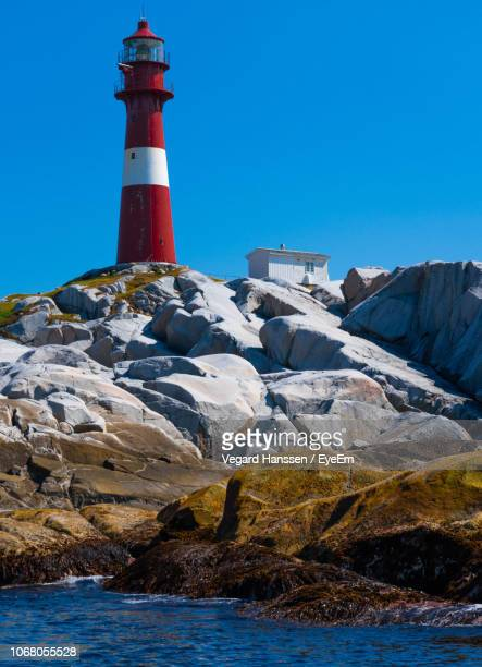 Lighthouse At Beach Against Clear Blue Sky