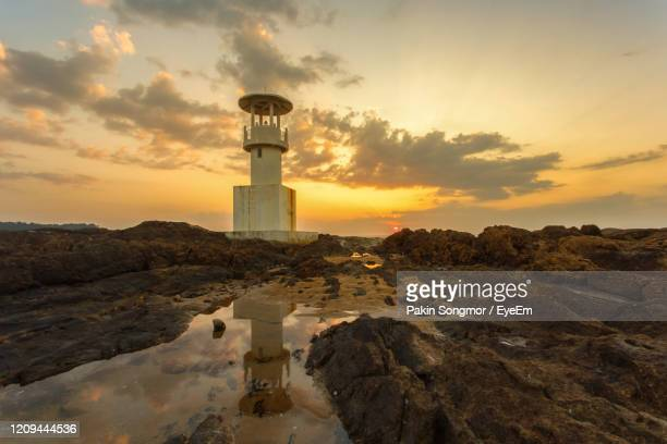 lighthouse at beach against sky during sunset - brunei stock pictures, royalty-free photos & images