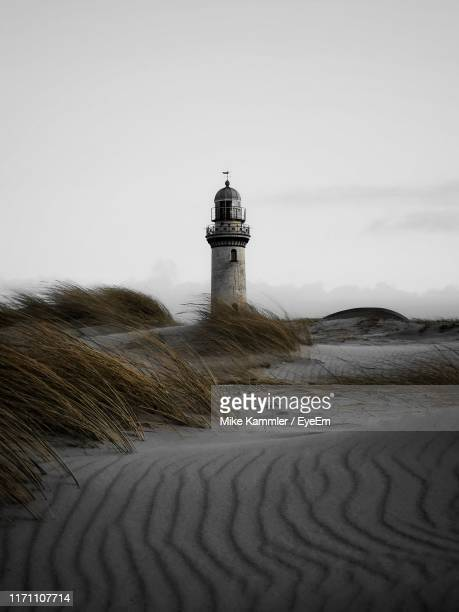 lighthouse at beach against sky - rostock stock pictures, royalty-free photos & images