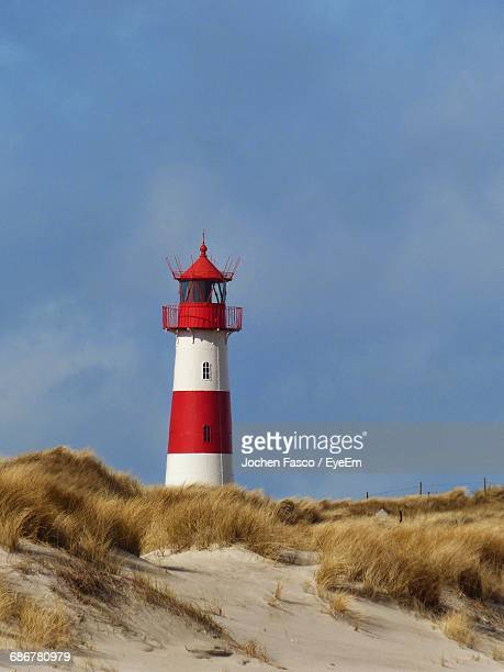 lighthouse at beach against sky - leuchtturm stock-fotos und bilder