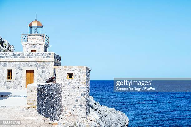 lighthouse at monemvasia in sea against clear sky - peloponnese stock photos and pictures