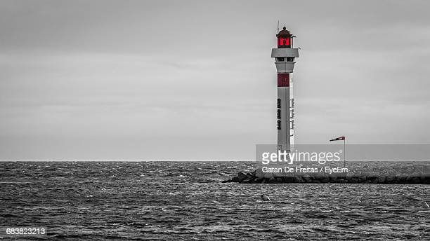 Lighthouse At Sea Shore Against Sky