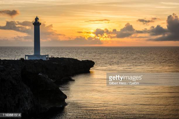 lighthouse at seaside during sunset - 防波堤 ストックフォトと画像