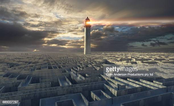 lighthouse beaming above distant maze - leuchtturm sturm stock-fotos und bilder