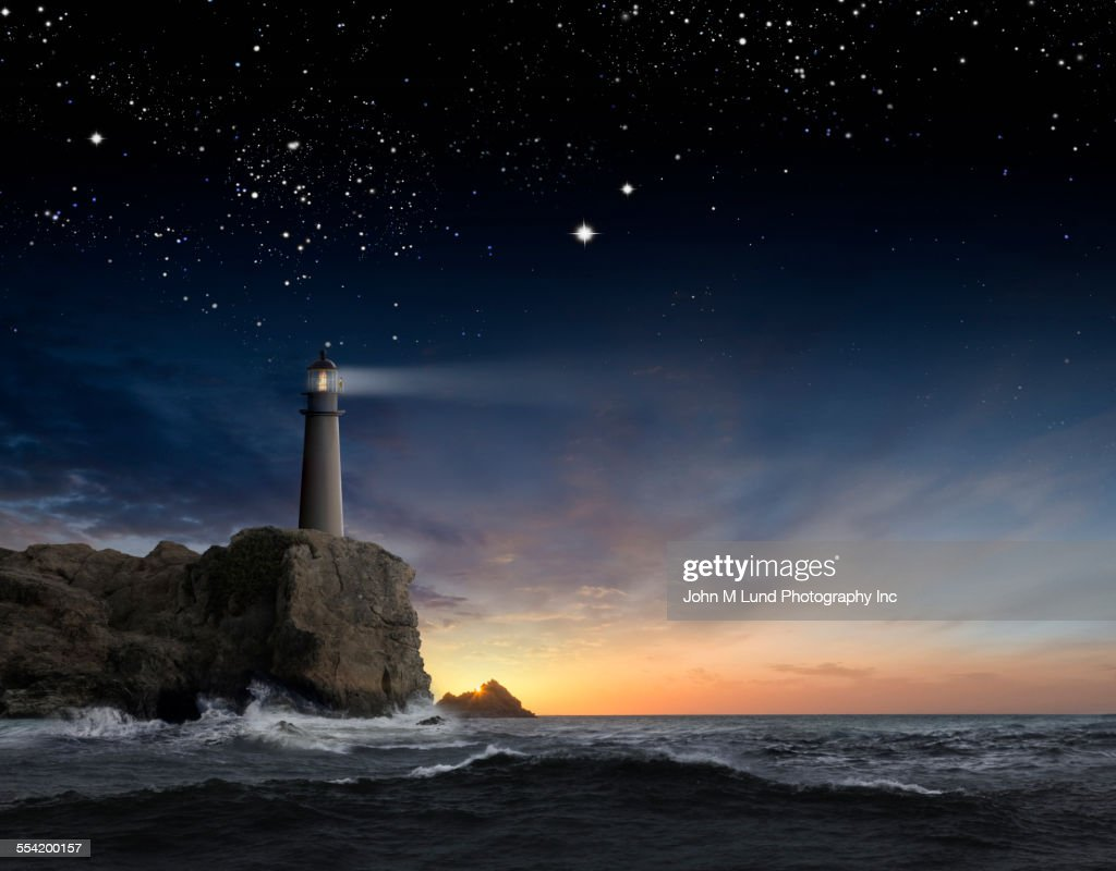 Lighthouse beaming over rocky ocean waves under sunrise sky : Stock Photo