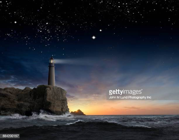 Lighthouse beaming over rocky ocean waves under sunrise sky