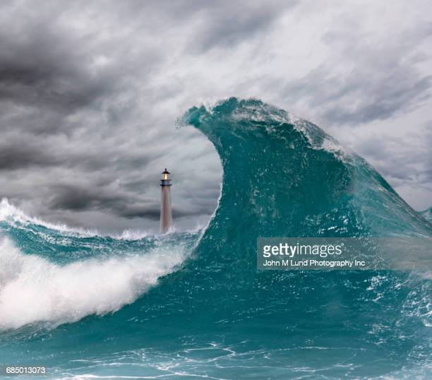 Lighthouse behind enormous wave in ocean