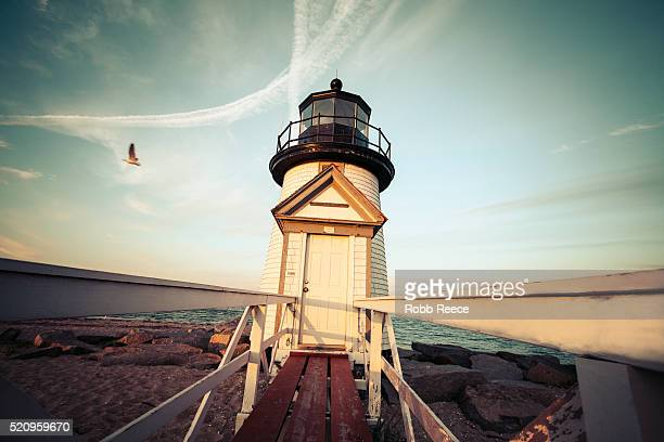 lighthouse building and beach at brant point on nantucket island - robb reece stockfoto's en -beelden