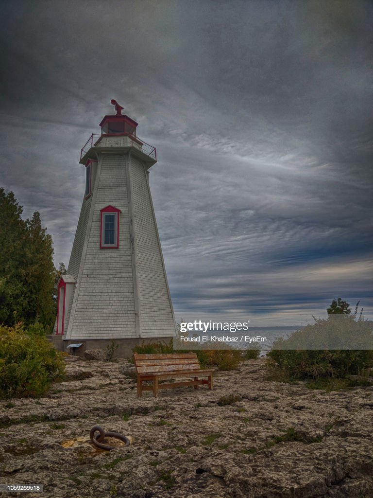Lighthouse By Building Against Sky : Stock-Foto