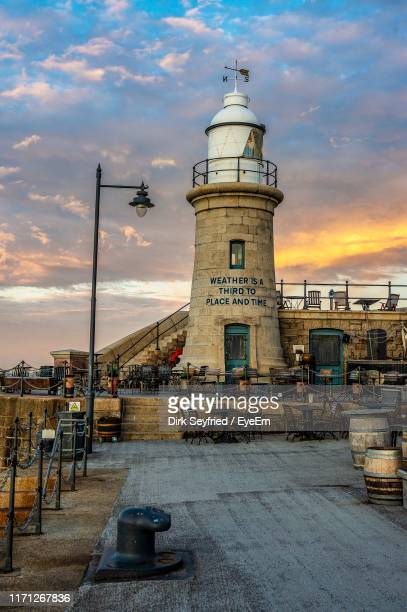 lighthouse by buildings against sky at sunset - folkestone stock pictures, royalty-free photos & images