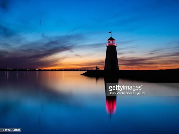 lighthouse by lake against sky during sunset - oklahoma city stock pictures, royalty-free photos & images