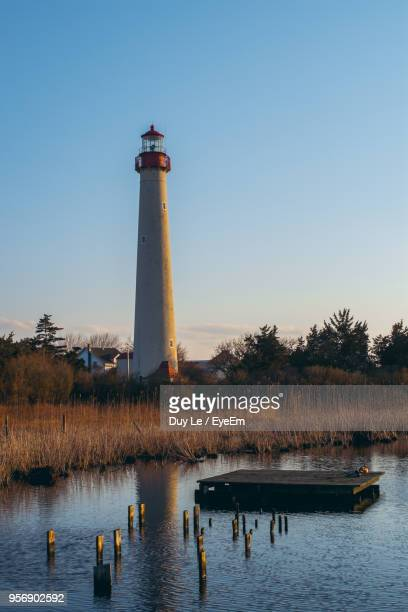 lighthouse by lake against sky - cape may stock pictures, royalty-free photos & images
