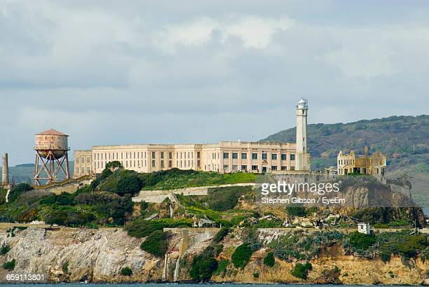 lighthouse by prison at alcatraz island against sky - alcatraz stock photos and pictures