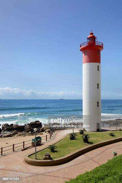 lighthouse by sea against blue sky - durban beach stock photos and pictures