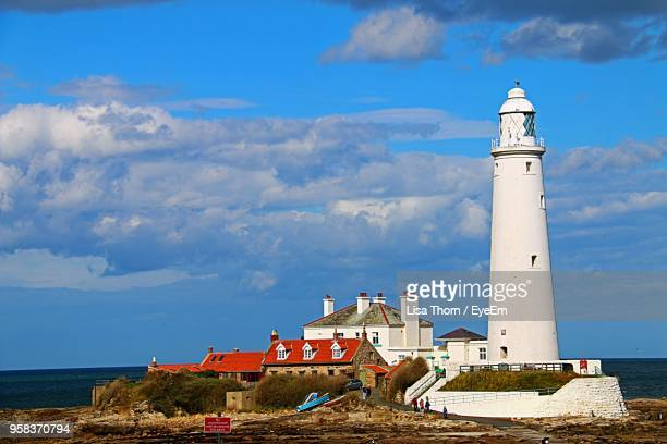 lighthouse by sea against blue sky - whitley bay stock pictures, royalty-free photos & images