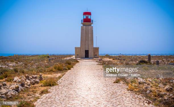 lighthouse by sea against clear blue sky - eriksen foto e immagini stock