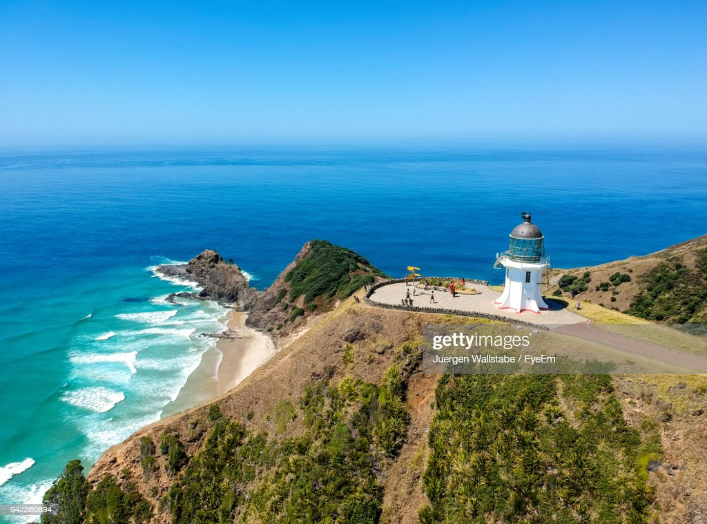 Lighthouse By Sea Against Clear Blue Sky : Stock Photo