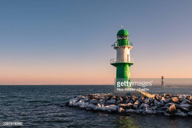 lighthouse by sea against clear sky during sunset - rostock stock pictures, royalty-free photos & images