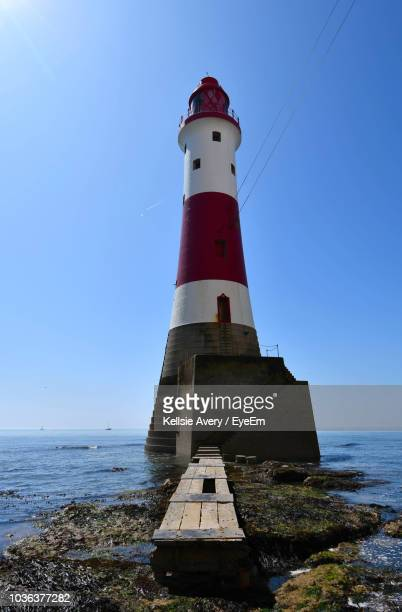 lighthouse by sea against clear sky - eastbourne stock pictures, royalty-free photos & images