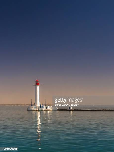 lighthouse by sea against clear sky - ウクライナ オデッサ市 ストックフォトと画像